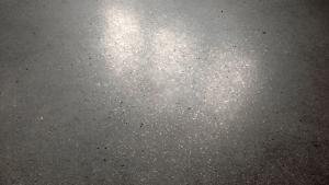 Poleret betongulv med guldstøv i badeværelse - nærbillede