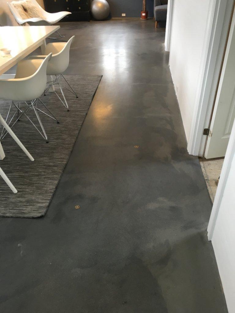 Mørk poleret betongulv med emblem